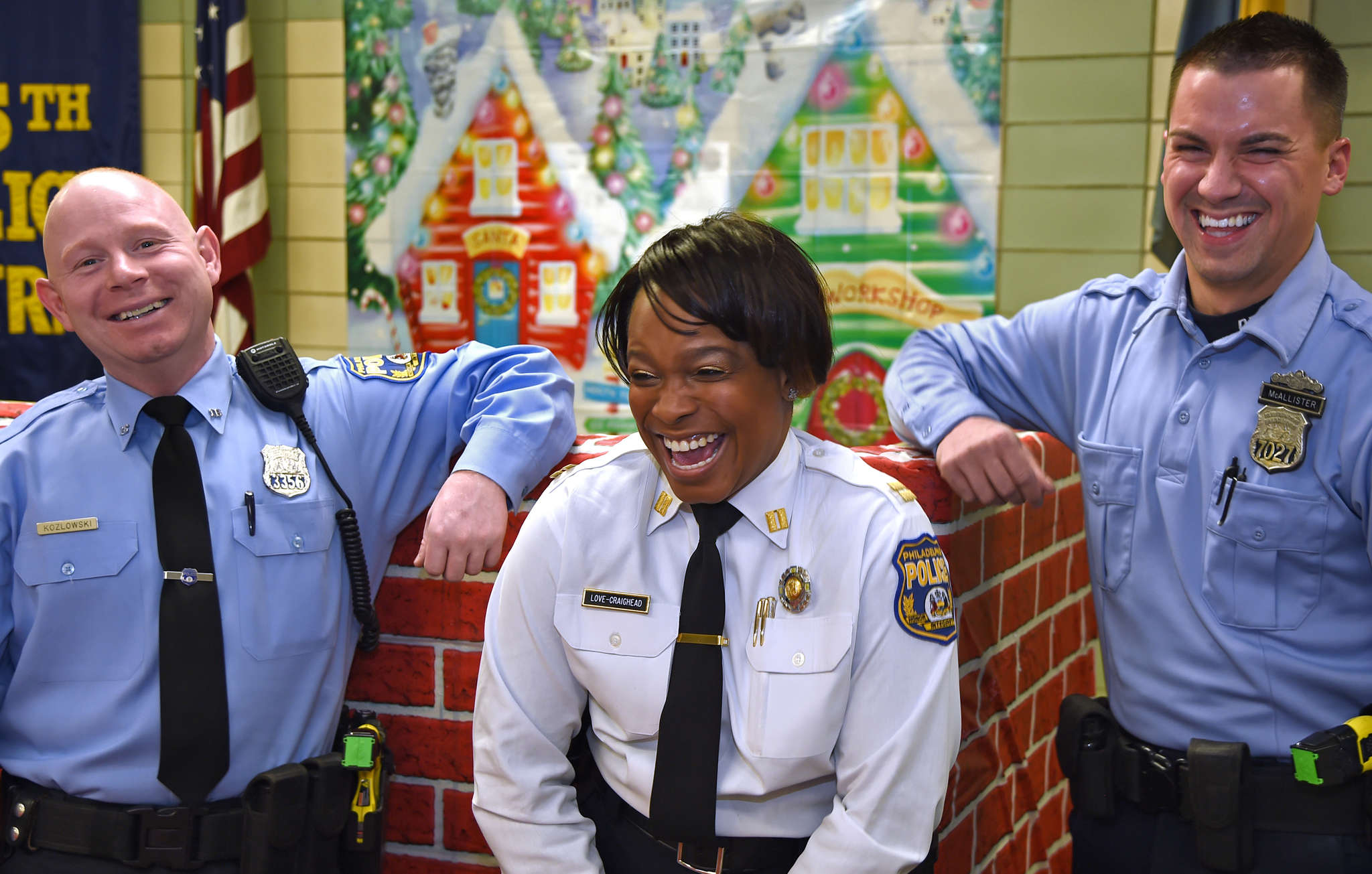After committing random acts of kindness, Officers Will Kozlwoski (left) and Sean McAllister are all smiles with Capt. Altovise Love-Craighead. TOM GRALISH / Staff Photographer