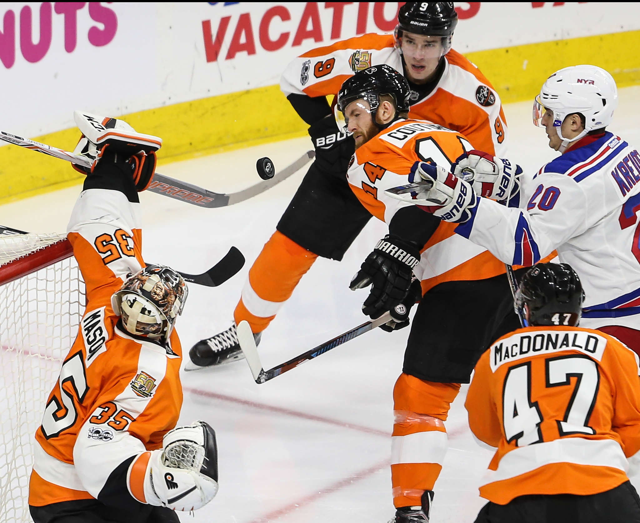 Flyers goalie Steve Mason deflects the puck in front of teammate Sean Couturier and the Rangers´ Chris Kreider. STEVEN M. FALK /Staff Photographer