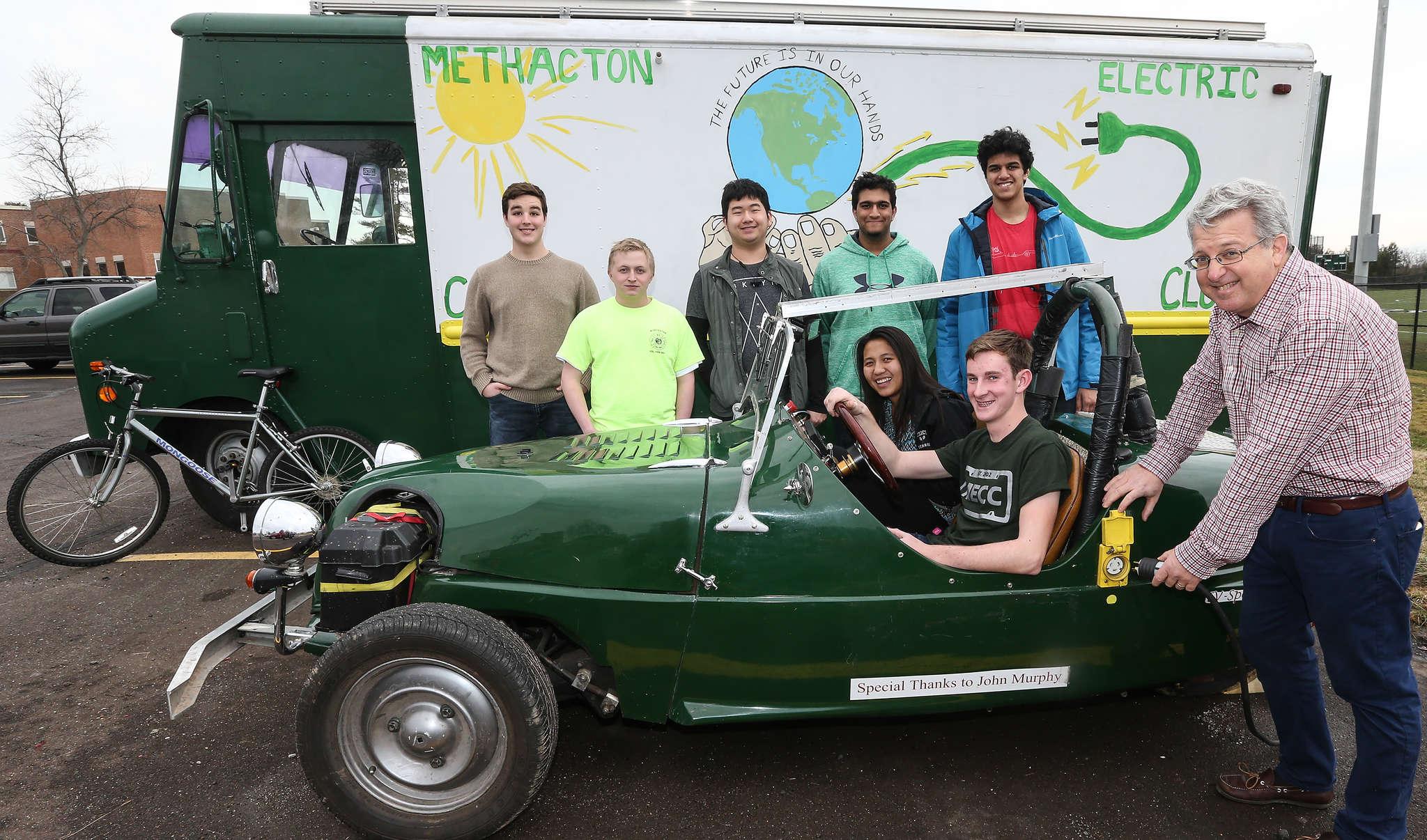 Sponsor Steve Savitz shows off the Lomax, with (in car) Amanda Amornwichet, Bryce Merrill, (from left) Jerrod Carney, Christian McIlhenny, Spencer Park, Satvik Kakkar, and Anuraag Nadkarni, at Methacton High School.