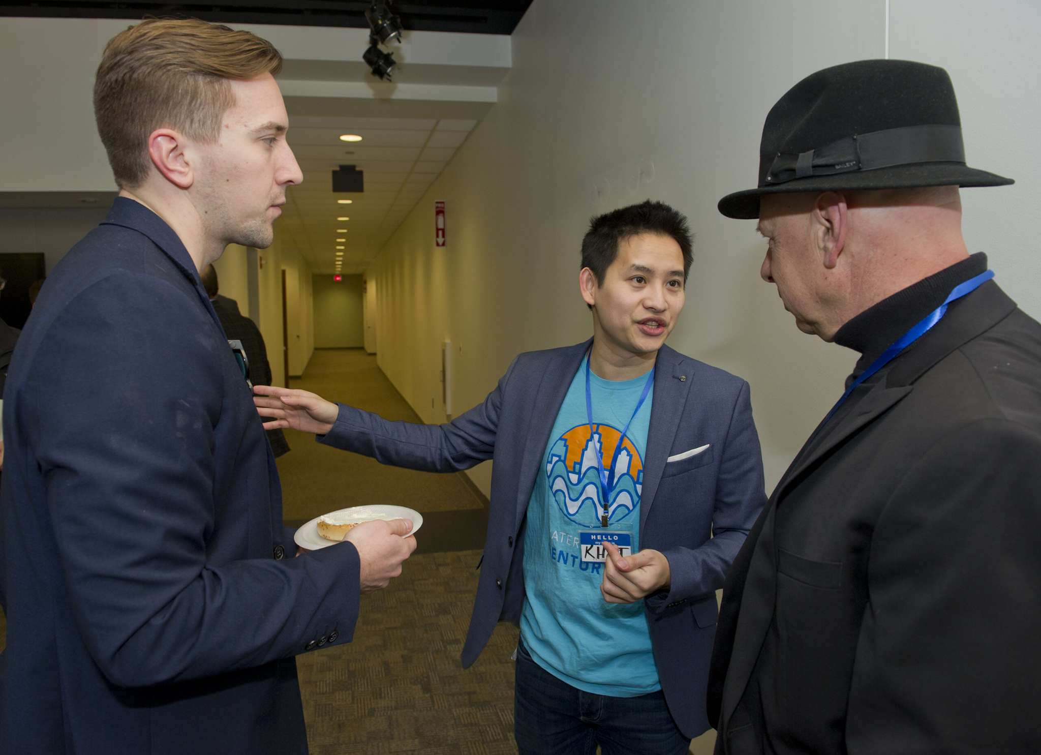 Johnathan Grzybowski, left, and Khai Tran, founders of Waterfront Ventures, speak with attendee Zave Smith, right, co-founder of the Xhilarate design firm in Philadelphia, during the UP Conference at the Waterfront Technology Center in Camden.