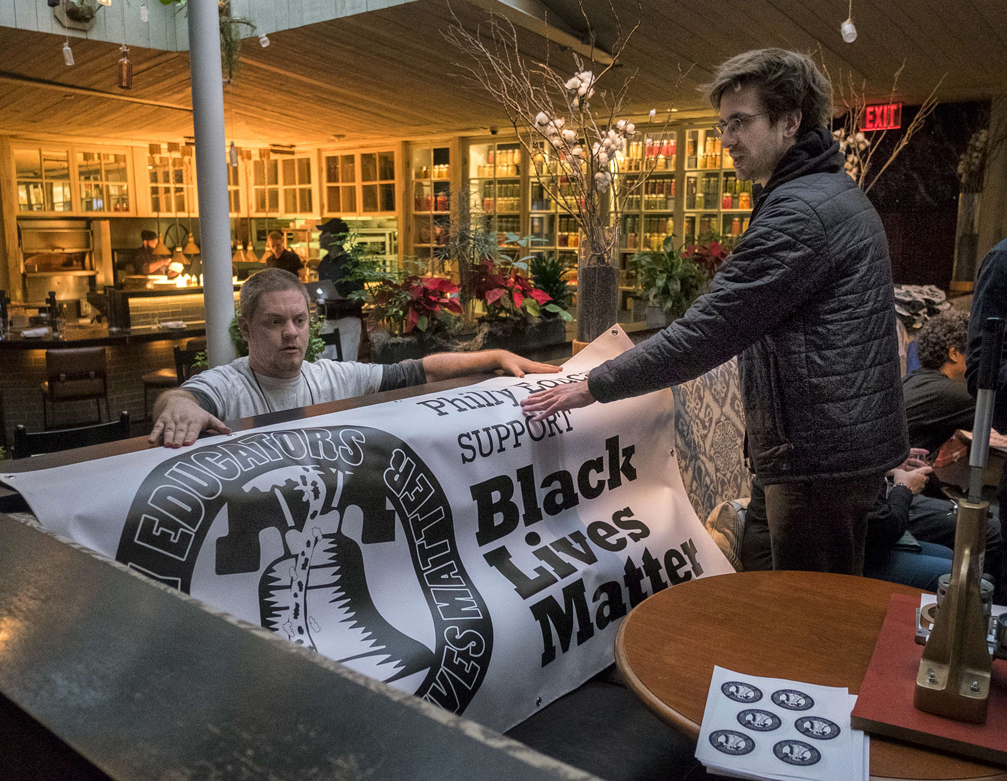 Members of the Caucus of Working Educators, an activist group of Philadelphia teachers, drape a Black Lives Matter banner at South restaurant, where they met to plan optional activities and curriculum for classes.