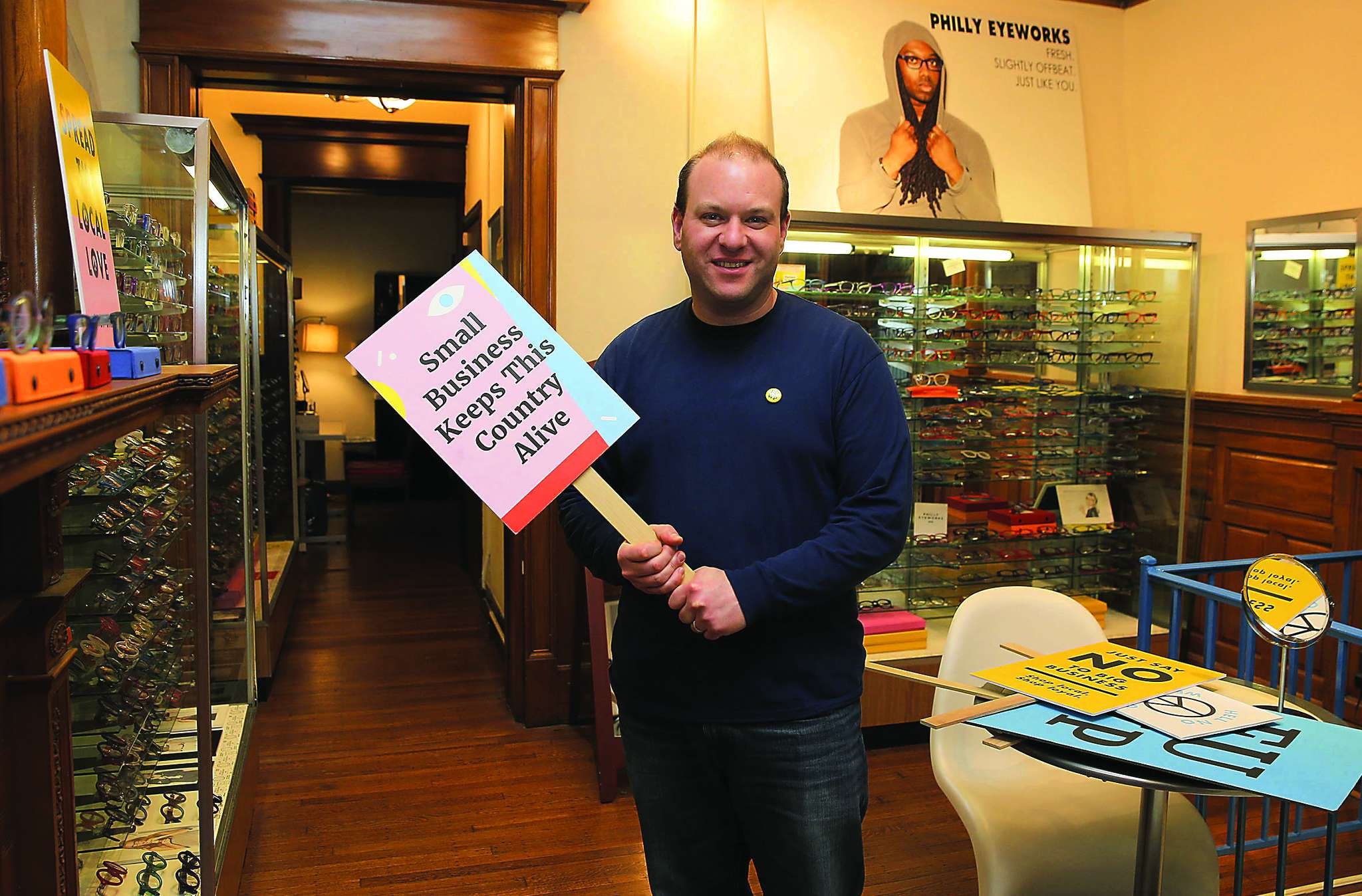 Clifton Balter in his eyewear store with a sign promoting local small businesses. He plans to greet the new Warby Parker store with his message.