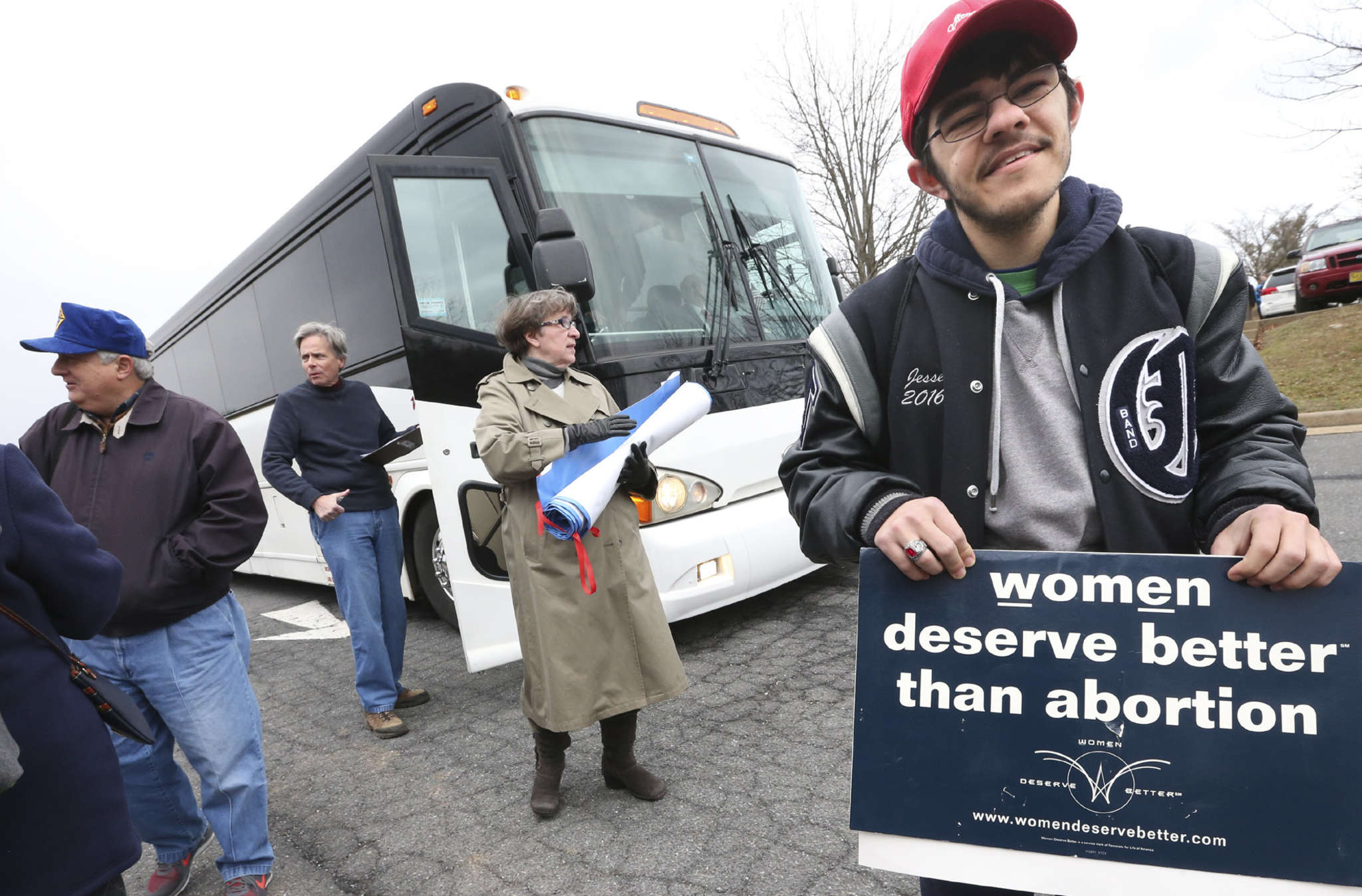 Jesse Davis holds a sign before boarding a bus in Winchester, Va., for the March for Life rally. JEFF TAYLOR / Winchester Star