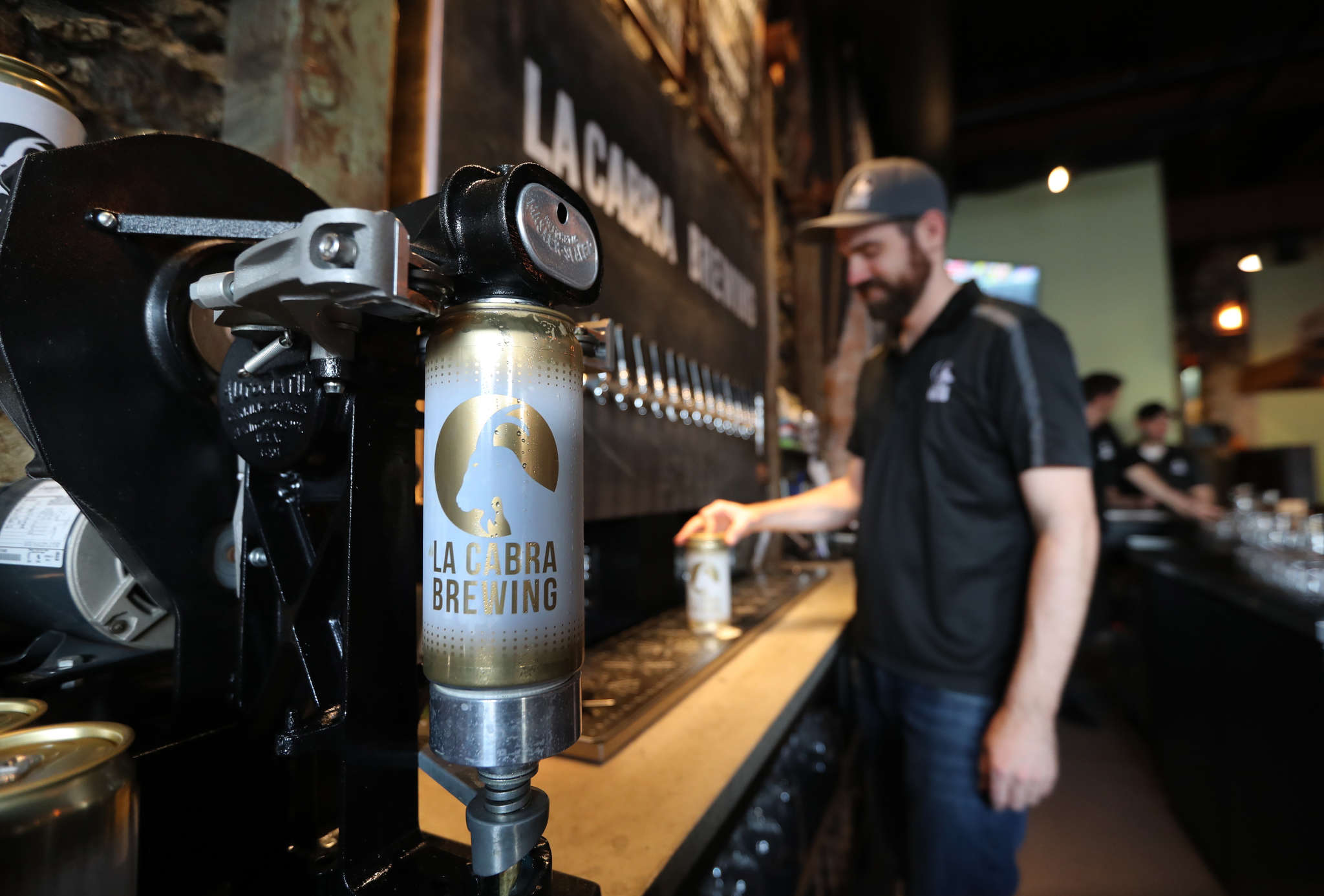 General manager Chuck Golder fills a growler at La Cabra Brewing, Dan Popernack´s four-month-old brewpub on Lancaster Avenue.