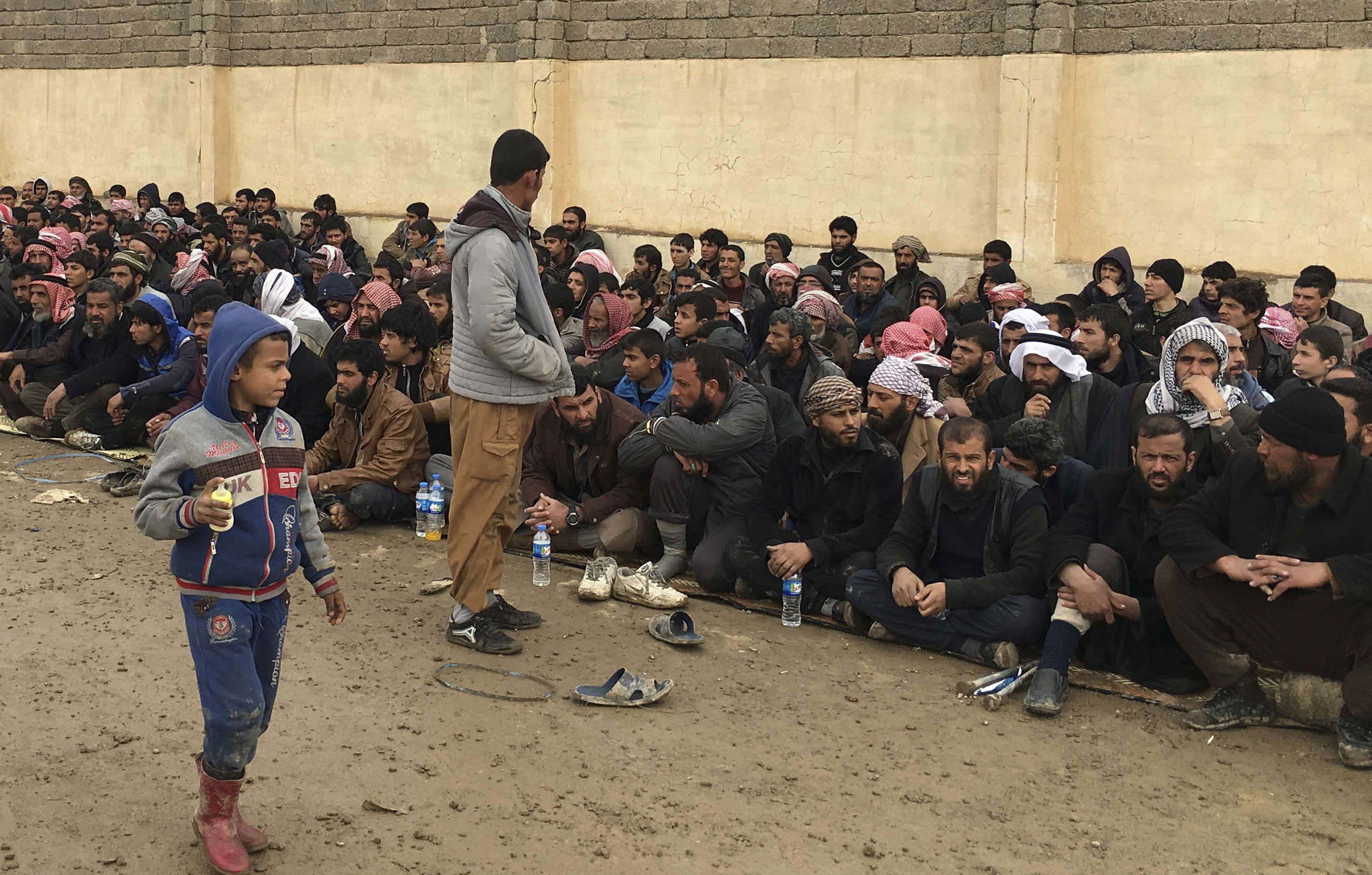 Displaced Iraqis wait for a security check at an Iraqi army base.