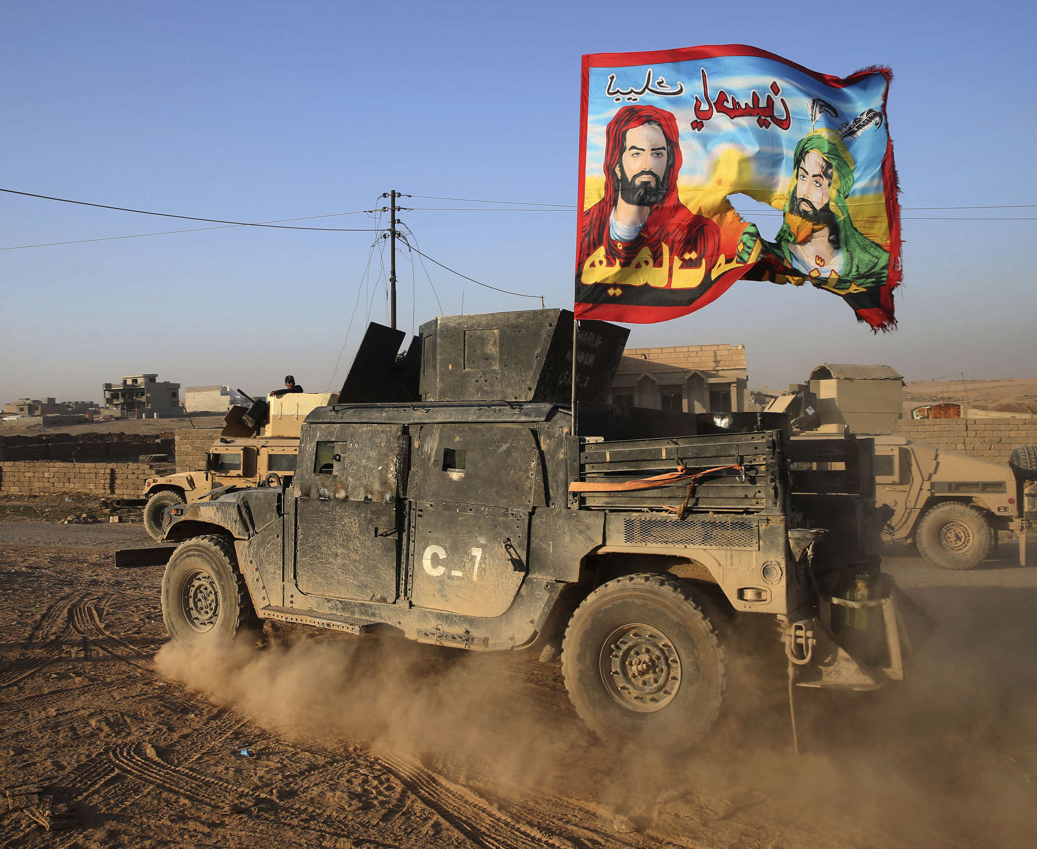 An Iraqi military vehicle in Mosul bears a Shiite flag with the likenesses of Imams Hussain and Ali and a message of fealty to Hussain.