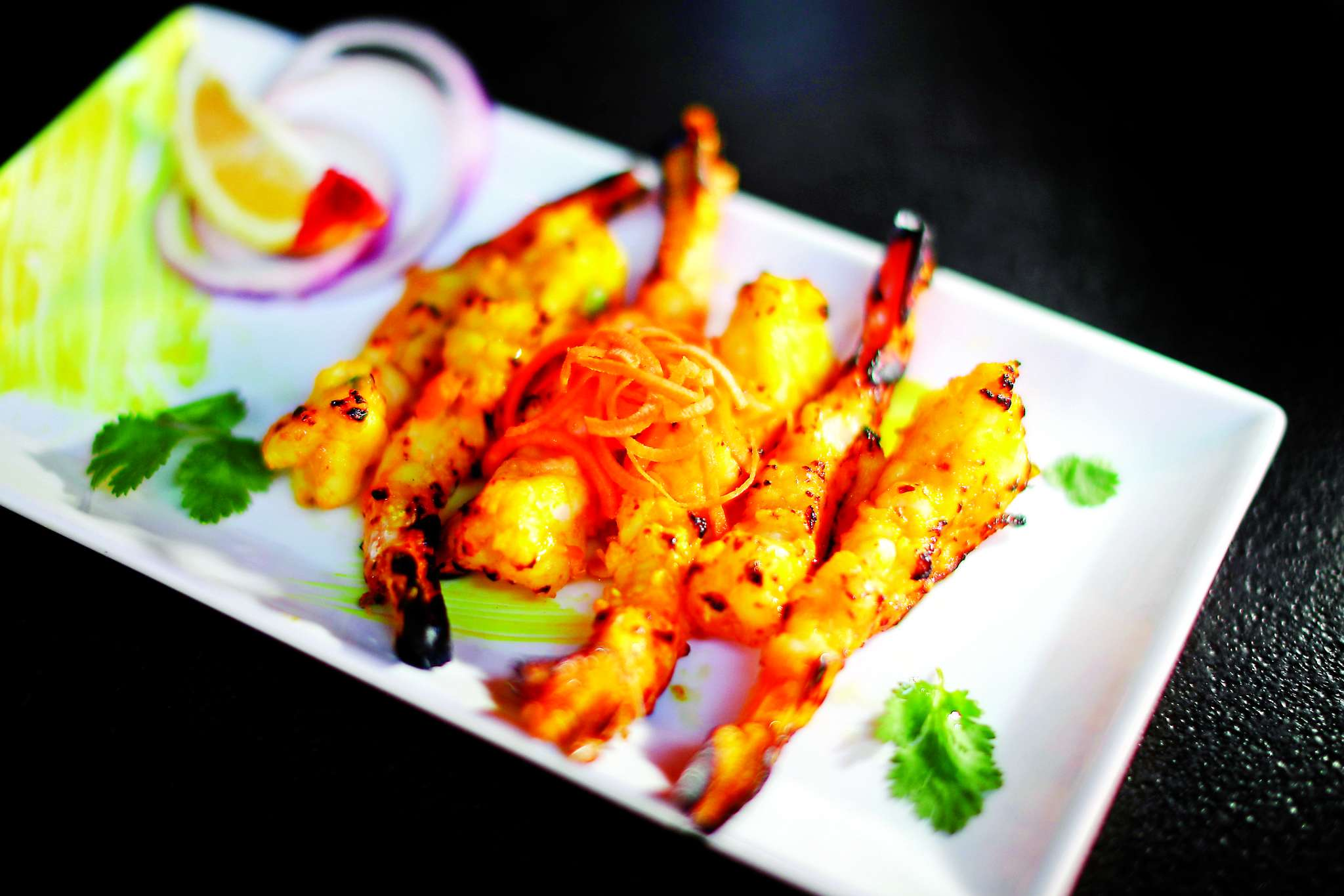 Grilled tandoori shrimp served with a yogurt marinade at Veda.