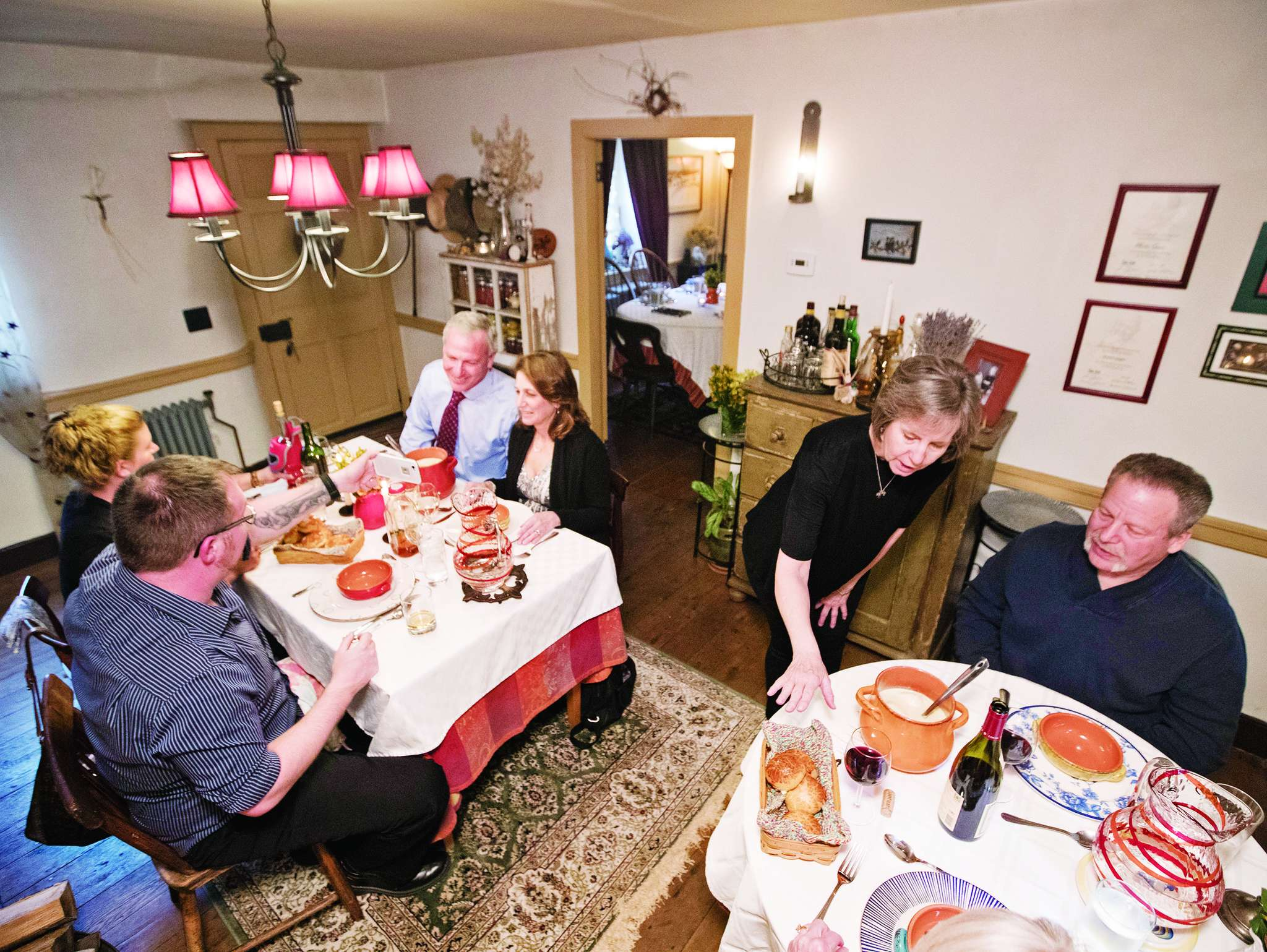 At La Maison, a French country auberge in Chester County, Janet Gagné - wife of chef/owner Martin Gagné - describes the first two courses to Michael Friedland (right) and other patrons.