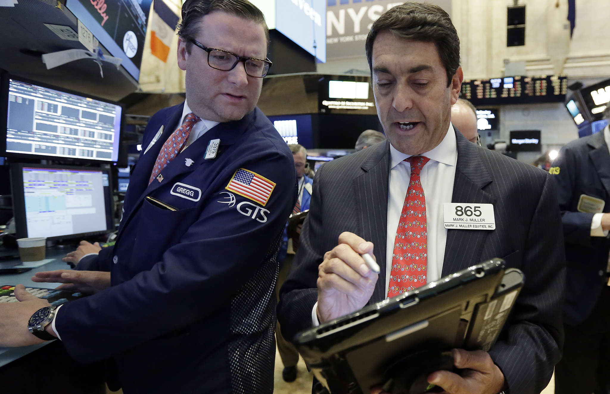 Gregg Maloney and Mark Muller (right) on the NYSE floor. Banks bucked the broader market decline, and oil rose for the fourth straight day.