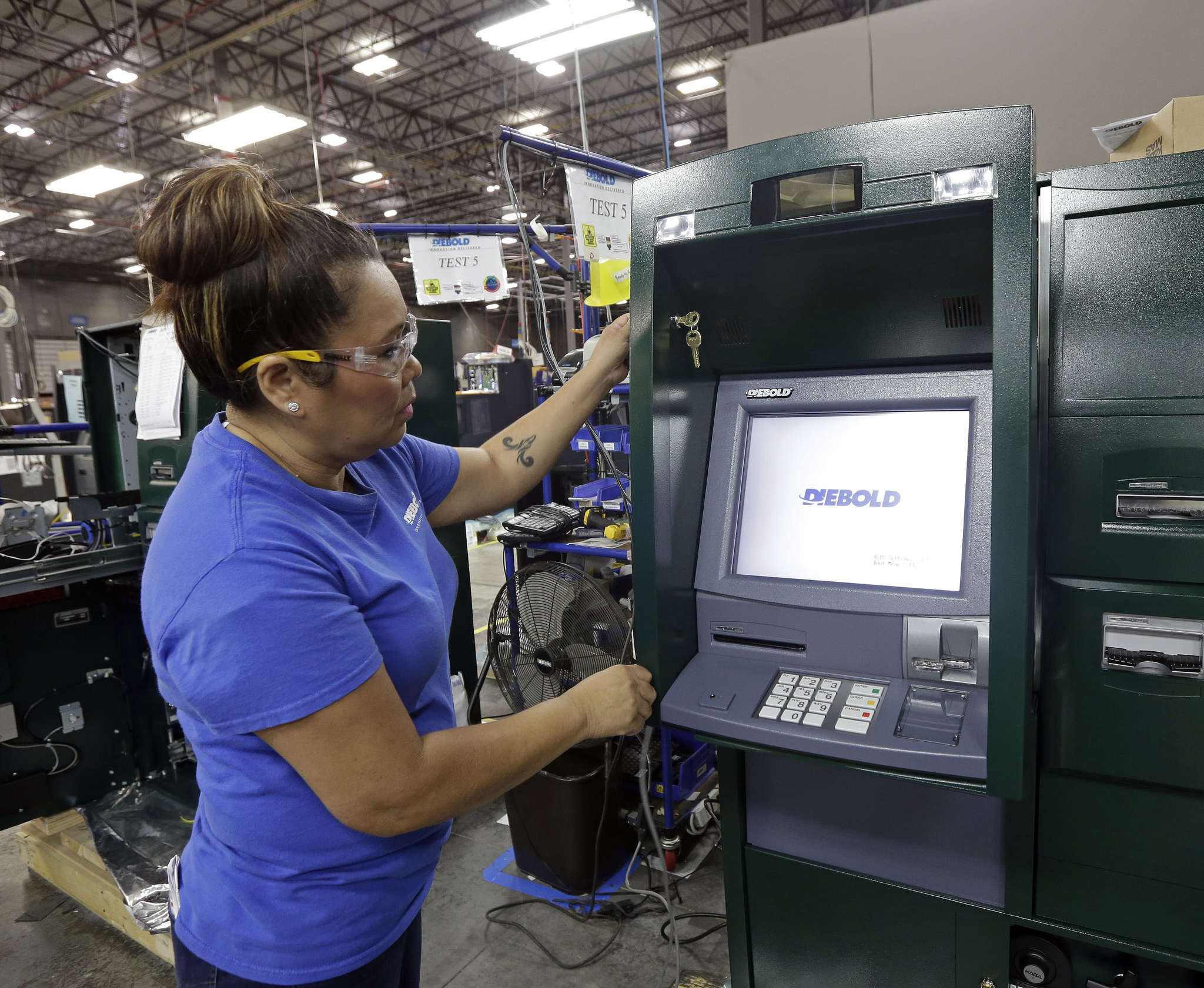 Maria Edney installs software onto an automated teller machine at Diebold Nixdorf, the world´s largest maker of ATMs, in Greensboro, N.C.