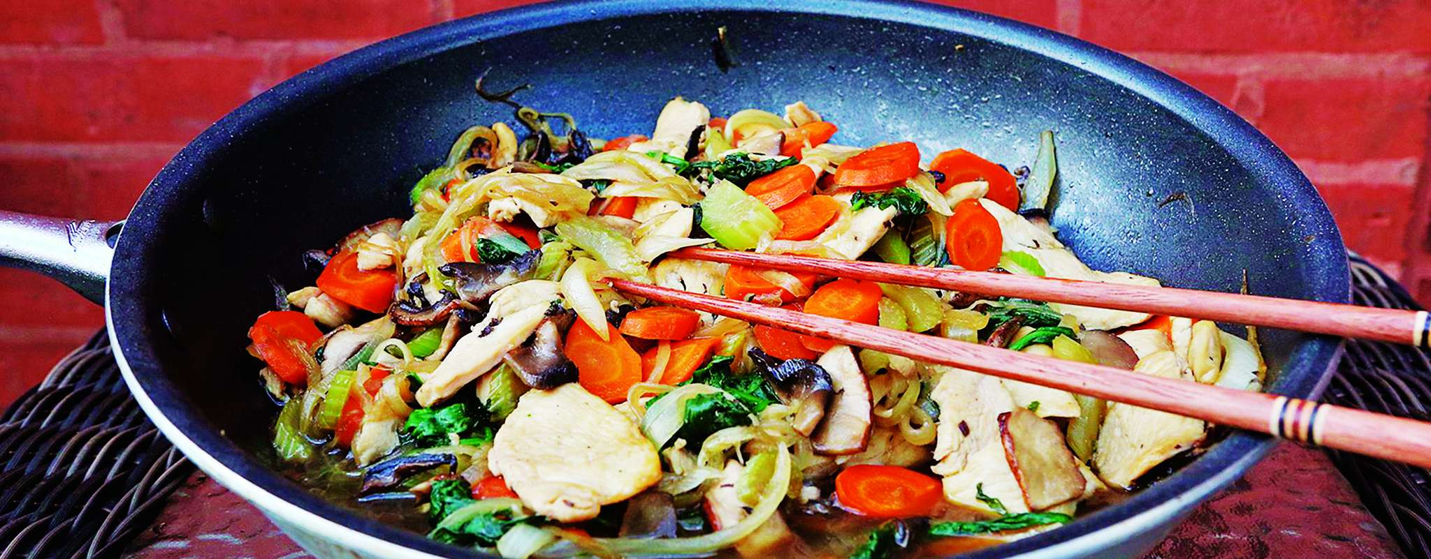 Chicken sukiyaki uses little broth but a wealth of vegetables: onion, carrots, celery, spinach, mushrooms, and bamboo shoots.