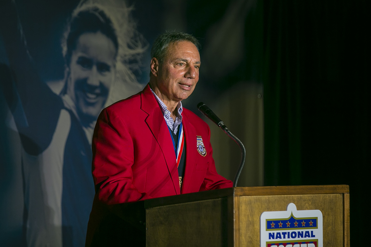 Tony DiCicco, shown here speaking during National Soccer Hall of Fame induction ceremonies in March, has died.
