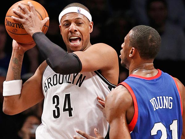 Paul Pierce looks to pass around Thaddeus Young. (AP Photo/Kathy Willens)