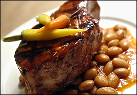 The pork chop entree, tender and moist with a bewitching barbecue sauce, is served on a bed of cranberry beans and topped with baby carrots.                                      (Michael Perez/Inquirer)