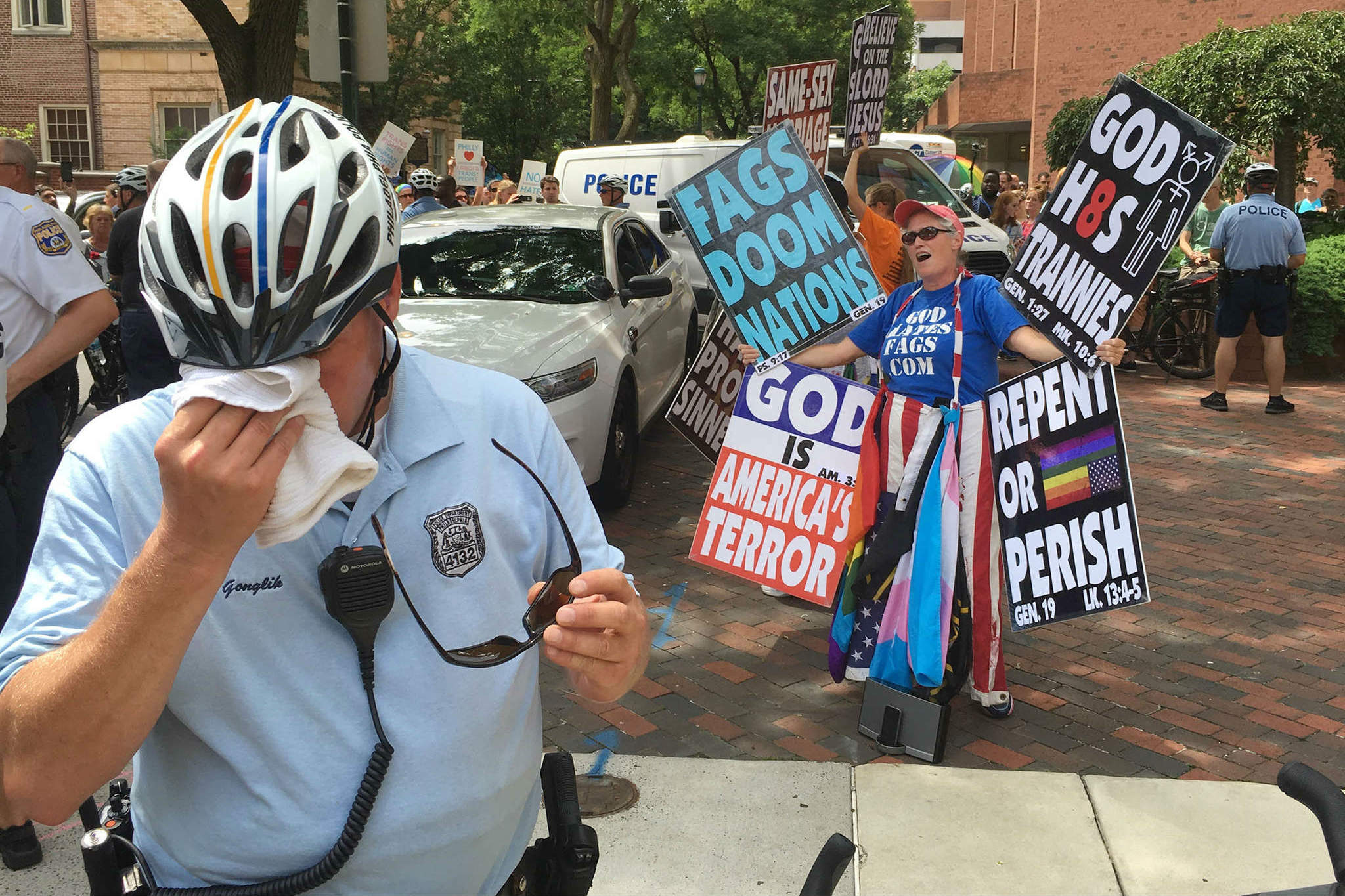 A policeman wipes his face as Westboro Baptist Church members protest at Eighth and Locust Streets. Dozens showed up for a counterprotest. Occupy DNC Rally and March at FDR Park is scheduled through 7:30 p.m. today.