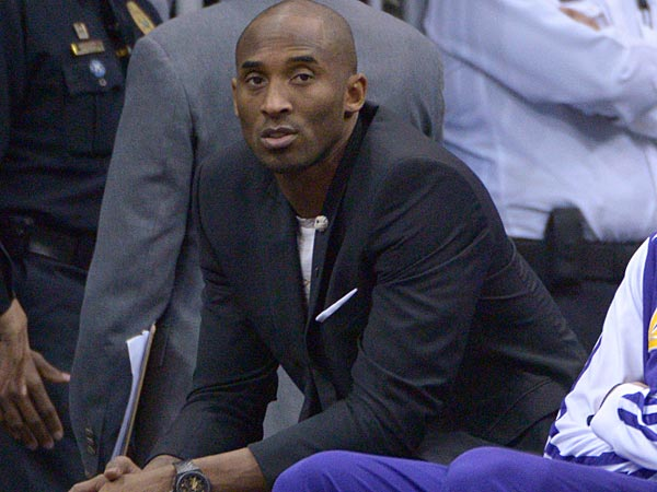 Los Angeles Lakers shooting guard Kobe Bryant, left, watches from the<br />end of the bench as a teammate takes a shot during the first half of<br />an NBA basketball game against the Orlando Magic in Orlando, Fla.,<br />Friday, Jan. 24, 2014.(AP Photo/Phelan M. Ebenhack)