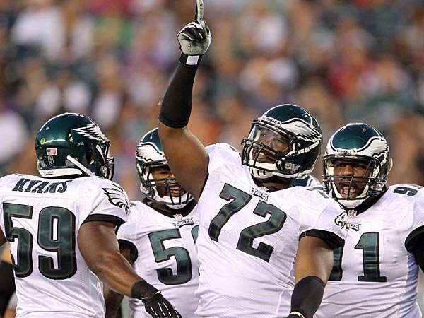 Cedric Thornton points to the sky after a stop with teammates<br />DeMeco Ryans (left), Trent Cole and Fletcher Cox (right). (Yong Kim/Staff file photo)