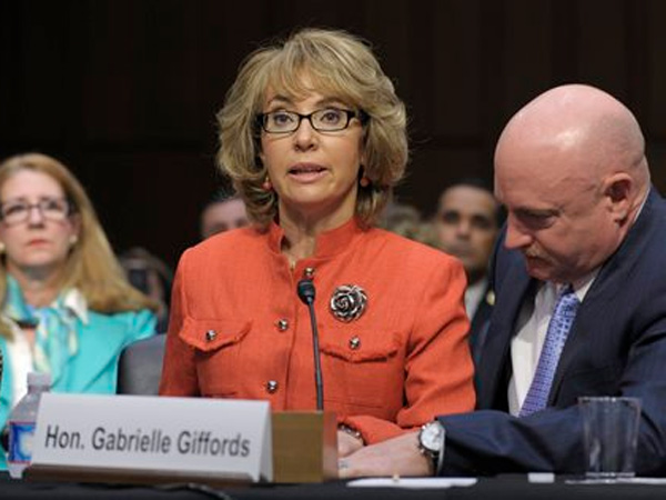 FILE - In this Jan. 30, 2012 file photo, former Arizona Rep. Gabrielle Giffords is aided by her husband, Mark Kelly, as she speaks before the Senate Judiciary Committee hearing on gun violence  (AP Photo/Susan Walsh, File)