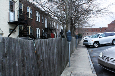 A fence separates West Athens Avenue residents´ backyards from the current Cricket Lot where a 145-apartment structure may sit within three years. (Ashley Nguyen / Philly.com)