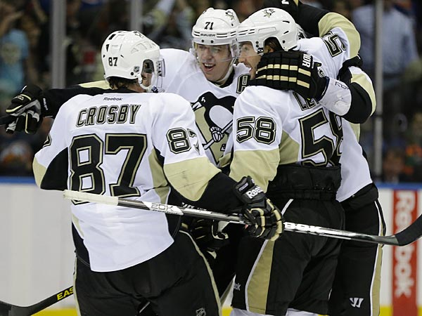Pittsburgh Penguins center Sidney Crosby (87), defenseman Kris Letang (58) and Penguins center Evgeni Malkin (71) of Russia after Pittsburgh defenseman Paul Martin, scored the tying goal in the third period of Game 6 of their first-round NHL Stanley Cup playoff hockey series in Uniondale, N.Y., Saturday, May 11, 2013. The Penguins went on to win 4-3 in overtime on Brooks Orpik´s goal. (AP Photo/Kathy Willens)
