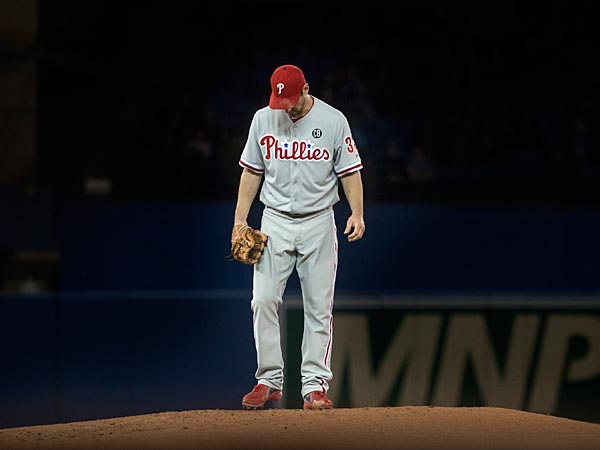 Cliff Lee takes a moment to consider tunneling out of the stadium. (AP Photo/The Canadian Press, Chris Young)
