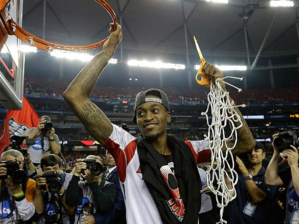 Louisville guard Kevin Ware holds the net after Louisville defeated Michigan 82-76 after the second half of the NCAA Final Four tournament college basketball championship game Tuesday, April 9, 2013, in Atlanta. (AP Photo/David J. Phillip)