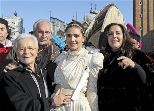 FILE-  This Sunday, Feb. 15, 2009 file photo shows Margherita Missoni, at center in white, the granddaughter of Rosita, left, and Ottavio Missoni, second from left, and designer Angela Missoni, Margherita&acute;s mother, right, after Margherita performed the traditional &quot;Flight of the Angel&quot; hanging from a cable tied from the bell tower to  St. Mark&acute;s Square in Venice, northern Italy.  It&acute;s all about the jet-setter life on Rodeo Drive in Beverly Hills, Calif, and next week multiple generations of Missonis as well as supermodel Iman will land there. They&acute;re the newest honorees of the Rodeo Walk of Style, which gives fashion influencers a permanent place to celebrate their signature looks.   (AP Photo/Luigi Costantini, File)<br />
