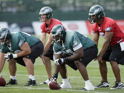Eagles quarterbacks Donovan McNabb (right) and A.J. Feeley prepare to take snaps from Jamaal Jackson and Dallas Reynolds (left) during training camp. (Yong Kim / Staff Photographer)
