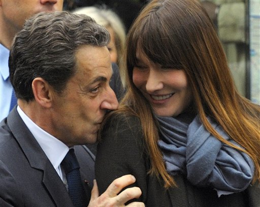 FILE - In this May 6, 2012 file photo, French President and UMP candidate Nicolas Sarkozy kisses his wife Carla Bruni-Sarkozy as they are greeted by supporters after casting their votes in the second round of French presidential elections in Paris. After Carla-Bruni Sarkozy, the top model turned songstress known for her free-wheeling lifestyle, here she is, Valerie Trierweiler. The intelligent, elegant twice-divorced journalist, with a perfume of scandal in her past, will become the first unwed partner of a French head of state to enter the Elysee Palace. (AP Photo/Philippe Wojazer, Pool, File)<br />