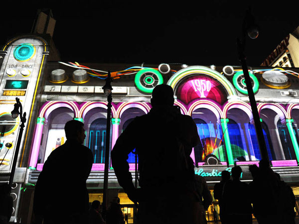 "Spectators enjoy the kinetic ""Boardwalk Beat"" show projected on Boardwalk Hall, the images and music heating up a cool Atlantic City night."