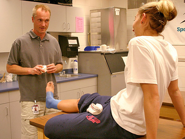 Jon Darling, athletic trainer for North Fargo, N.D. Spartan High School, tapes senior Marlee Nasset´s ankle prior to track practice, Friday, May 14, 2004. (AP Photo/Alyssa Hurst)