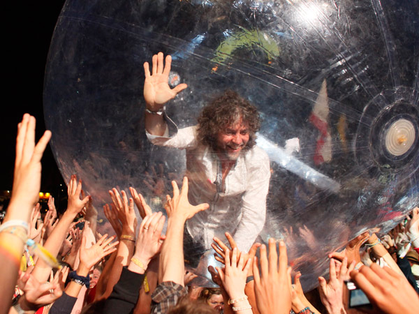 U.S. band The Flaming Lips, frontman Wayne Coyne takes a trip across the heads of the crowd inside a plastic bubble, as the band performs at Glastonbury Festival, in Glastonbury, England, Friday, June 25, 2010. The Festival celebrates its 40th anniversary this year. (AP Photo/Jim Ross)