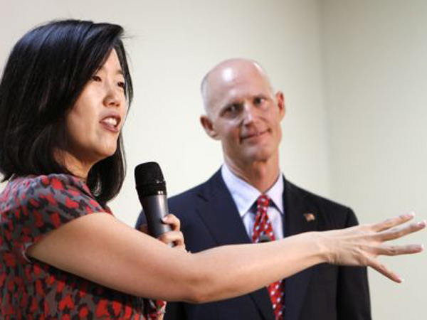 Michelle Rhee, left, speaks to staff and guests as Gov. Rick Scott looks on during a visit to a South Florida charter school in Opa-locka, Fla., January 2011. (Alan Diaz/AP)