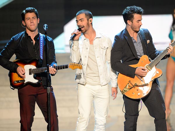 From left, recording artists Nick Jonas, Joe Jonas and Kevin Jonas of the Jonas Brothers perform onstage during the Miss USA 2013 pageant, Sunday, June 16, 2013, in Las Vegas. (AP Photo/Jeff Bottari)