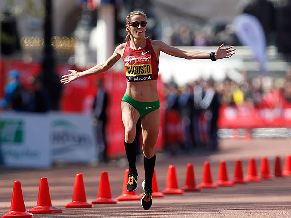 Jessica Augusto of Portugal stretches her hands out as she runs to the finish line during the London Marathon in London, Sunday, April 13, 2014. (AP Photo/Sang Tan)