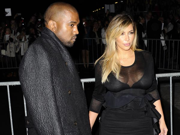 Kanye West, left, and Kim Kardashian arrive to attend Givenchy´s ready-to-wear Spring/Summer 2014 fashion collection, presented Sunday, Sept. 29, 2013 in Paris. (AP Photo/Zacharie Scheurer)