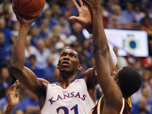 Kansas center Joel Embiid (21) shoots over Iona forward Daniel Robinson (44) during the first half of an NCAA college basketball game at Allen Fieldhouse in Lawrence, Kan., Tuesday, Nov. 19, 2013. (AP Photo/Orlin Wagner)
