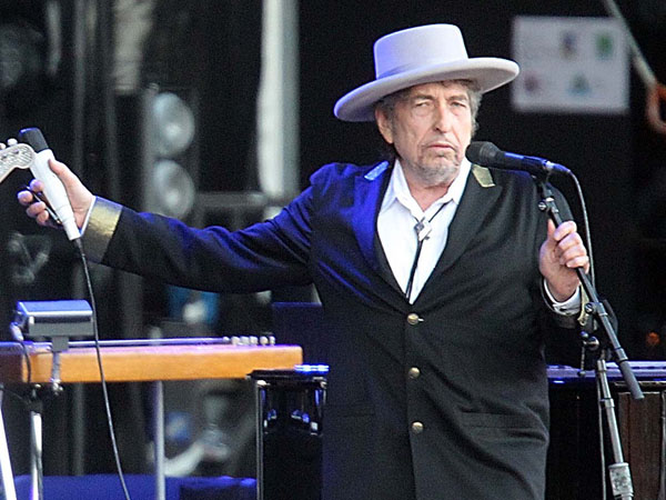 """This July 22, 2012 file photo shows U.S. singer-songwriter Bob Dylan performing on at """"Les Vieilles Charrues"""" Festival in Carhaix, western France.   It´s a crowded tour market and everyone is competing for your entertainment dollar. Dylan put together the Americanarama Festival of Music with My Morning Jacket and Wilco. (AP Photo/David Vincent, file)"""