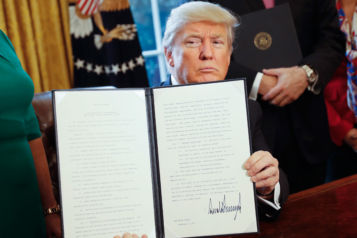 President Trump holds up an executive order in the Oval Office Feb. 3, 2017, that directs the Treasury secretary to review the 2010 Dodd-Frank financial oversight law, which reshaped financial regulation after 2008-2009 crisis.