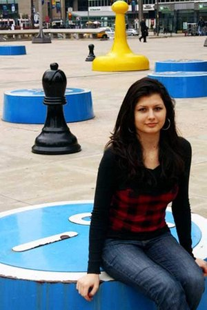Alisa Melekhina sits in front of a chess piece sculpture outside the Municipal Services Building. (Photo: Bob Reynolds).