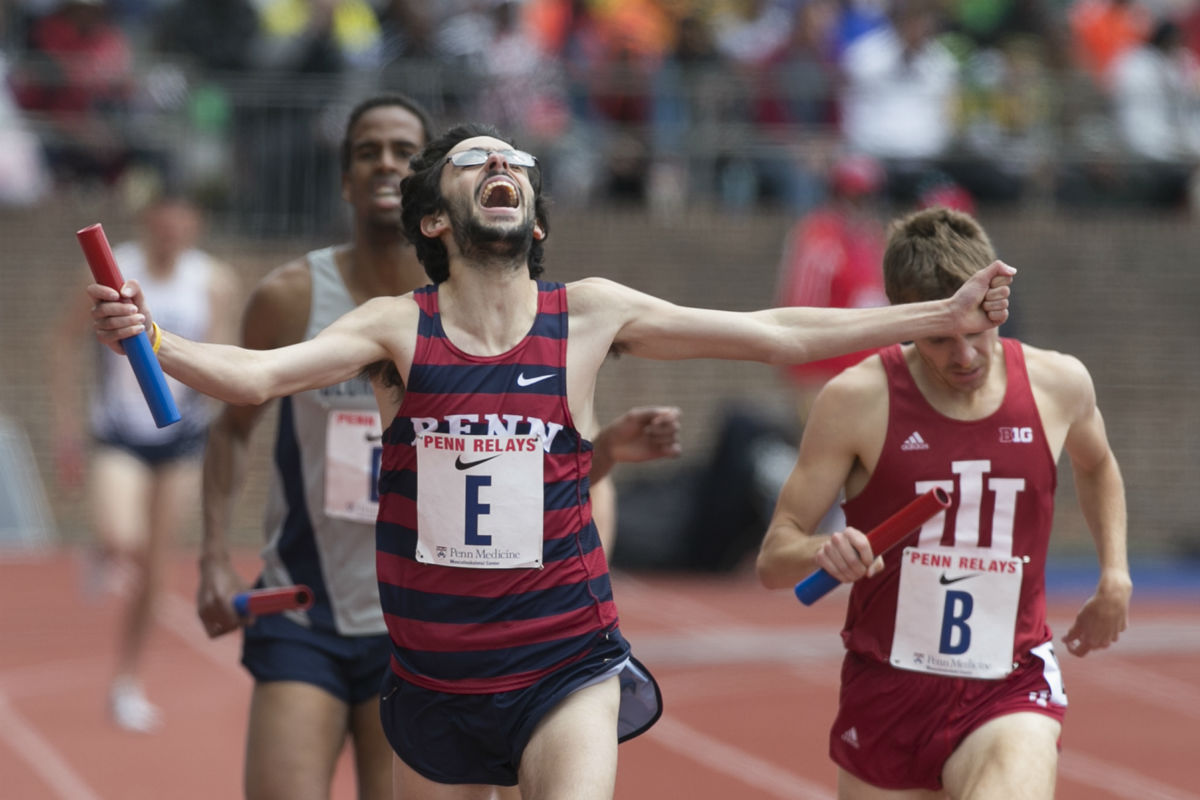 Penn´s Thomas Awad celebrates as he crosses the finish line ahead of Indiana´s Jason Crist (right) and wins the 4xmile Championship of America with relay teammates Keaton Naff, Chris Hatler and Nick Tuck.