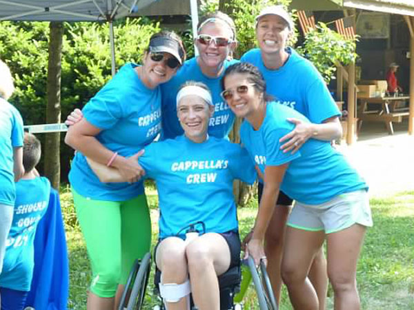 Jessica Cappella in her sports wheelchair with her cheering section after completing the Queen of the Hill triathlon.