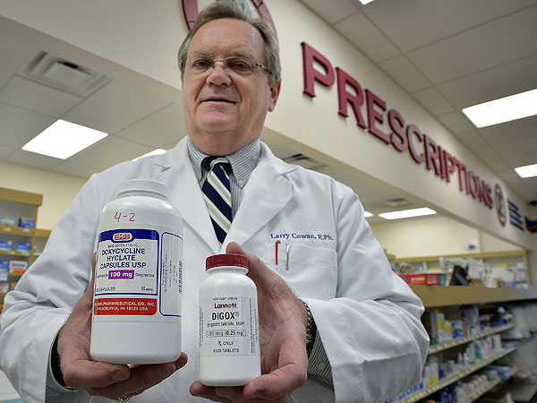 Pharmacist Larry Cowan holds bottles of Doxycycline Hyclate and Digox at Glenview Professional Pharmacy in Richland Hills, Texas, on April 17, 2014. Cowan can flip through his records and spot the long-used generic drugs that have taken big price jumps in the past year or so. (Max Faulkner/Fort Worth Star-Telegram/MCT)