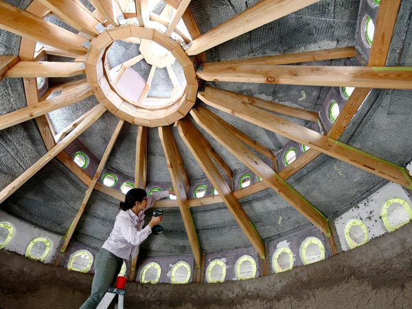 "Jessica Tong secures the windows along a spiral roof on a cob house under construction in San Jose, Calif., March 20, 2014. The 120-square-foot structure will become a hobby room once it is finished. Proponents for ""cob wall"" buildings assert that they are more sustainable and kill fewer trees than traditional wood frame construction. (Gary Reyes/Bay Area News Group/MCT)"
