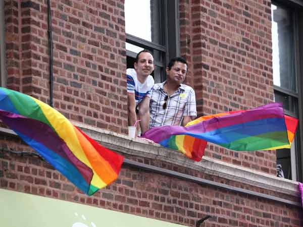 Two men watch from the window of an apartment as Jennifer Hudson performs at Chicago Pride Fest in the Lakeview neighborhood of Chicago, Ill., on Saturday, June 21, 2014. (Chris Sweda/Chicago Tribune/MCT)
