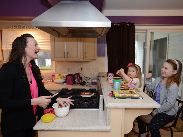 Carrie Hennessy, left, with daughters Caileigh, 7, right, and Leia, 4, in the kitchen of their new home in Ramsey, N.J., Jan. 11, 2014. ( Michael Karas/The Record/MCT)