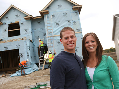 Mike and Ann Jeweson, both in the twenties, are taking advantage of low interest rates to make the four-bedroom home under construction behind them their first home. (Kyndell Harkness / Minneapolis Star Tribune / MCT)