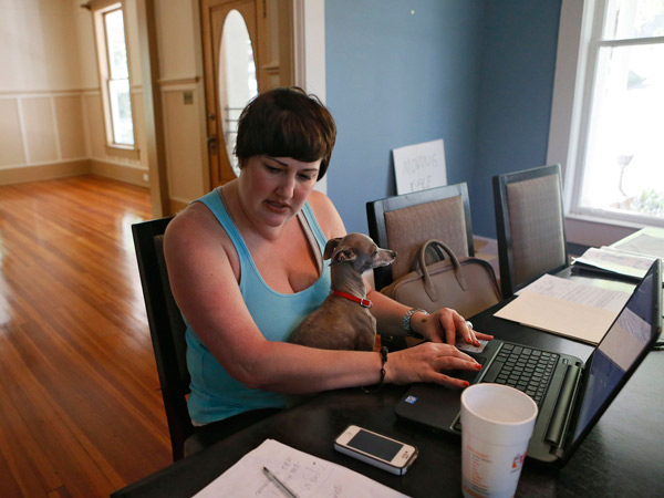 """Velvet Bradley works part-time at the dining room table in her home, with her Italian Greyhound, """"Sterling,"""" in her lap, while editing a magazine, April 22, 2014, in Rockmart, Ga. The living room behind her is empty because her house has been foreclosed on and she is in the process of moving out. (Bob Andres/Atlanta Journal-Constitution/MCT)"""
