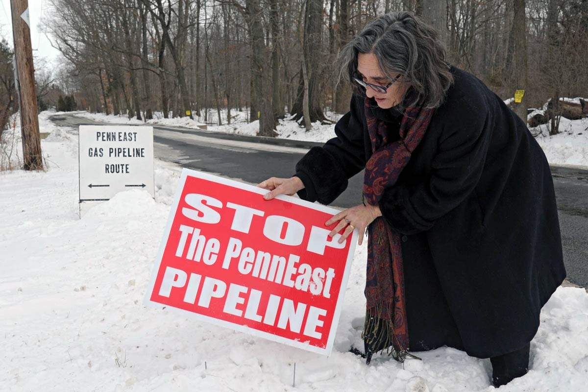 File: Alix Bacon adjusting an anti-pipeline placard in January 2015 in Hunterdon County, N.J., near where the proposed PennEast Pipeline would cross the road.