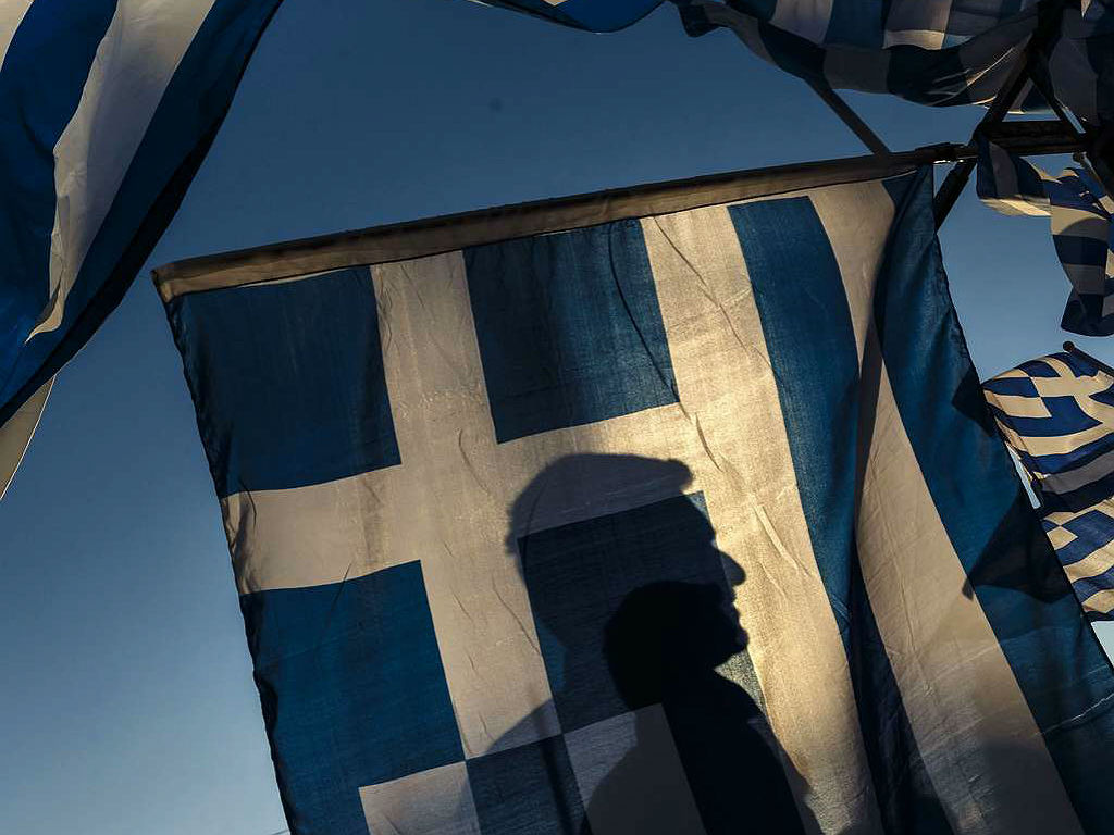 Is that Stu's silhouette behind a Greek flag outside the Greek Parliament in Athens? (Associated Press)<br />